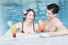 Портрет пары усмехаясь и выпивая коктеиль в бассейне Стоковые Фотографии RF