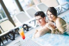 Портрет пары усмехаясь и выпивая коктеиль в бассейне Стоковое Изображение RF