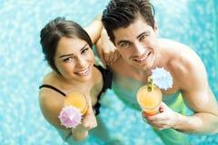Портрет пары усмехаясь и выпивая коктеиль в бассейне Стоковое Изображение