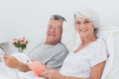 Портрет пары читая совместно в кровати Стоковые Изображения
