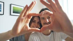 Портрет пар делая сердце с их руками смотря камеру и усмехаться сток-видео
