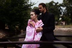 Портрет пар - девушки гейши в нежном розовом кимоно и кавказском человеке Стоковые Изображения RF