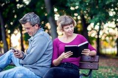 Портрет пар сидя снаружи Женщина читая книгу, укомплектовывает личным составом нас стоковое изображение
