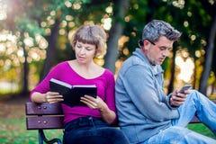 Портрет пар сидя снаружи Женщина читая книгу, укомплектовывает личным составом нас стоковое фото