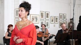 Портрет певицы в красном элегантном платье поет песню оперы на скрипачах и проводнике предпосылки на зале видеоматериал