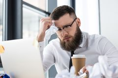 портрет перегружанного бизнесмена на рабочем месте с компьтер-книжкой и кофе, который нужно пойти Стоковое Изображение RF