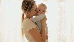 Портрет перед окном счастливой молодой матери держа ее милый усмехаясь ребёнок видеоматериал