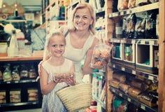 Портрет печений женщины и девушки радостно ходя по магазинам стоковые изображения