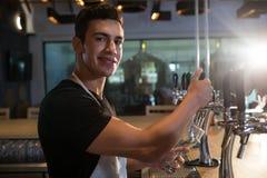 Портрет пива бармена лить от крана стоковое фото