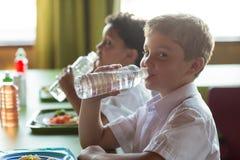 Портрет питьевой воды школьника от бутылки Стоковое Фото