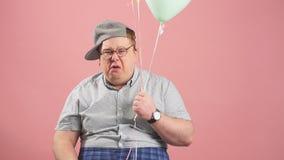 Портрет плача взрослого человека в серой случайной носке, держа воздушные шары на пинке акции видеоматериалы