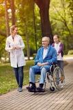 Портрет пожилого человека на кресло-коляске с медсестрой и granddaught Стоковое Изображение