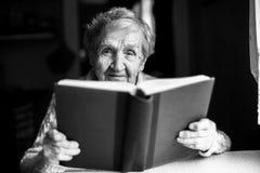 Портрет пожилой женщины читая книгу Стоковое Изображение RF
