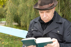 Портрет пожилого человека читая outdoors стоковое изображение rf