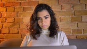 Портрет полностью смотрит на внимательной кавказской коммерсантки брюнета сидя на софе и работая с ноутбуком дома сток-видео