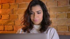 Портрет полностью смотрит на радостной кавказской коммерсантки брюнета сидя на софе и наблюдая smilingly в ноутбук на акции видеоматериалы
