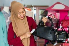 Портрет положения владельца и костюма азиатского hijab женского с черным портмонем в ее магазине моды бутика, молодое мусульманск стоковая фотография