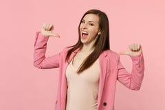 Портрет положения куртки жизнерадостной смешной женщины нося, указывая большие пальцы руки на себе на пастельной розовой стене стоковая фотография rf