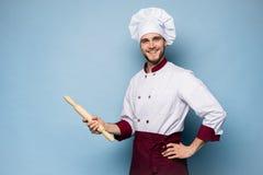 Портрет положительного зубастого повара шеф-повара в берете, белом обмундировании имея инструменты в пересеченных оружиях смотря  стоковое изображение