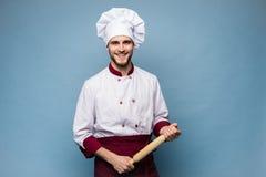 Портрет положительного зубастого повара шеф-повара в берете, белом обмундировании имея инструменты в пересеченных оружиях смотря  стоковые фотографии rf