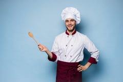 Портрет положительного зубастого повара шеф-повара в берете, белом обмундировании имея инструменты в пересеченных оружиях смотря  стоковые фото