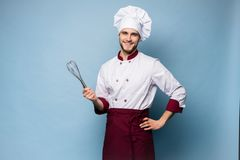 Портрет положительного зубастого повара шеф-повара в берете, белом обмундировании имея инструменты в пересеченных оружиях смотря  стоковое фото