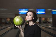 Портрет положительной девушки играя клуб боулинга Девушка с шариком боулинга в его руках стоковые фотографии rf