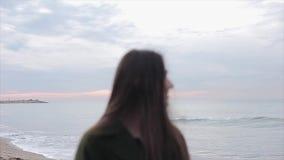 Портрет полу-тела красивой девушки с длиной освобождает темные волосы смотря к левой стороне пока стоящ на seashore на акции видеоматериалы