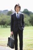 Портрет портфеля нося молодого бизнесмена стоя на парке Стоковые Изображения