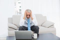 Портрет потревоженного зрелого бизнесмена с компьтер-книжкой дома Стоковая Фотография