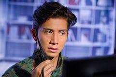 Портрет потревоженного молодого солдата нося военную форму, воинский оператора трутня наблюдая на его компьютере и использование Стоковое Изображение RF