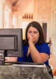 Портрет потревоженной тучной женщины работая на компьтер-книжке пока сидящ перед ее столом в офисе Стоковая Фотография RF