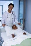 Портрет положения доктора пока пациент лежа на непредвиденной кровати растяжителя Стоковое Изображение RF
