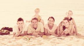 Портрет положительной семьи лежа совместно на пляже Стоковое Изображение RF
