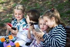 Портрет положительных детей играя с телефонами Стоковое Изображение