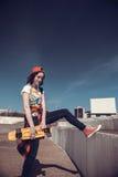 Портрет подростка в бейсбольной кепке и скейтборде Стоковое фото RF