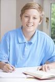 Портрет подростка делая домашнюю работу на таблице Стоковые Фото