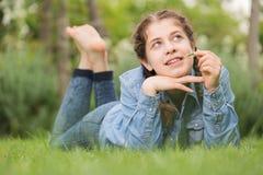 Портрет подростка пока лежащ в парке зеленого цвета лета Стоковые Фото