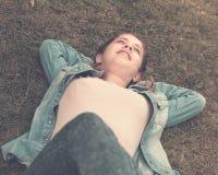 Портрет подростка пока лежащ в парке зеленого цвета лета Стоковые Изображения