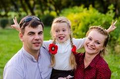 Портрет праздника внешний счастливой семьи обнимая и смеясь над на пикнике Стоковая Фотография