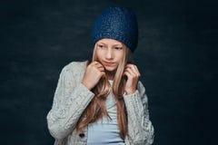 Портрет предназначенной для подростков девушки со светлыми волосами нося шляпу и свитер зимы стоковое изображение