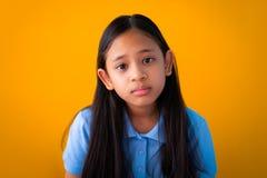 Портрет предпосылки серьезной азиатской милой девушки оранжевой стоковое фото