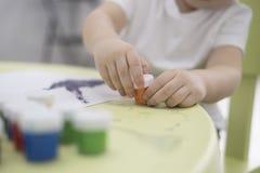 Портрет прелестного маленького азиатского мальчика держа paintbrush и работая на картине для художественного класса в школе довер Стоковые Фотографии RF