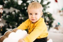Портрет прелестного маленького младенца усмехаясь на камере сидя на рождественской елке стоковые фотографии rf