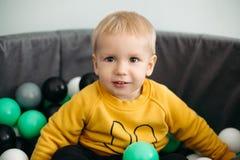 Портрет прелестного маленького младенца усмехаясь на камере сидя на рождественской елке стоковое фото