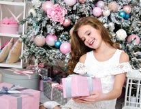 Портрет прелестного счастливого усмехаясь ребенка маленькой девочки в подарочной коробке удерживания платья принцессы стоковые изображения