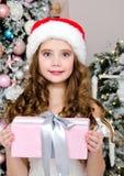 Портрет прелестного счастливого усмехаясь ребенка маленькой девочки в подарочной коробке удерживания шляпы santa около ели стоковое изображение rf