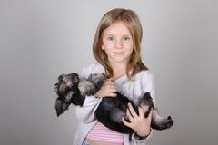 Портрет прелестной белокурой маленькой девочки усмехаясь держащ щенка шнауцера Стоковые Фотографии RF