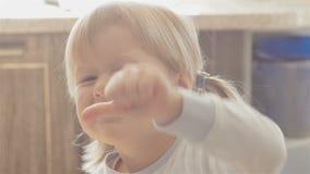 Портрет прелестной маленькой девочки с кабелями усмехаясь и показывая класс сидя на стуле в ее доме сток-видео