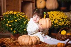 Портрет прелестной усмехаясь девушки представляя с оранжевой тыквой в интерьере падения деревянном Стоковые Фото